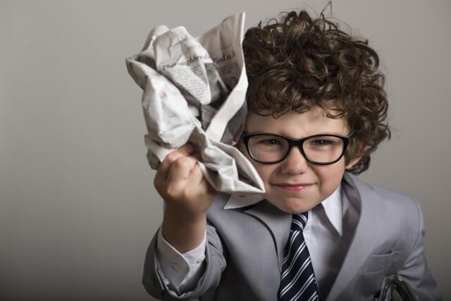 新聞をクシャクシャに丸める子供