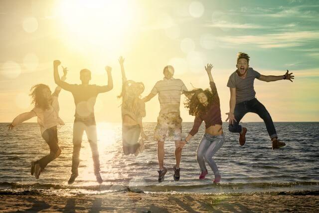 夕日が差す砂浜で大ジャンプをしてはしゃぐ6人の若者たち
