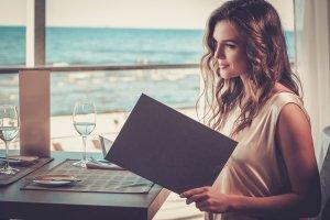 レストランでメニューを見る女性