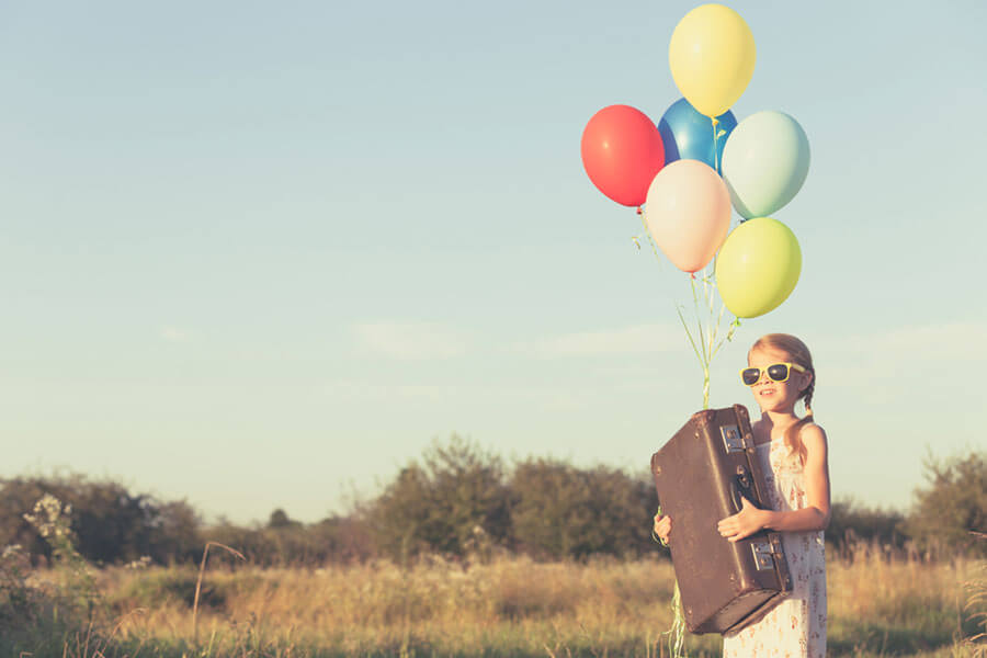 風船とトランクをもつ女の子