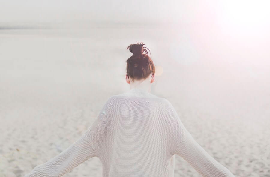 砂浜を歩く女性の後ろ姿