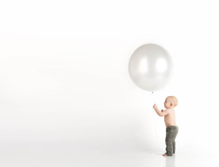 白い風船を持つ赤ちゃん